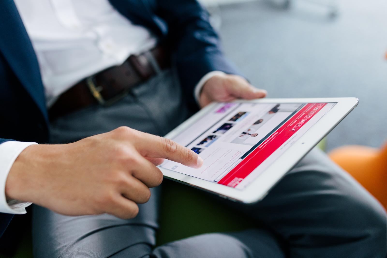 Person scrollt durch die HdM Website auf einem Tablet